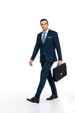 full length view of businessman with briefcase walking and looking at camera on white