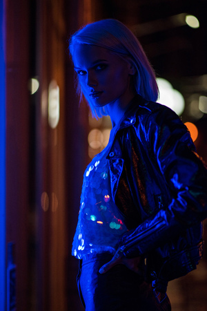 attractive young woman in glossy tank top and leather jacket on street at night under blue light Stock Photo