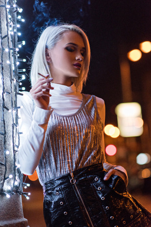 beautiful young woman smoking on street at night while leaning on wall with white garland