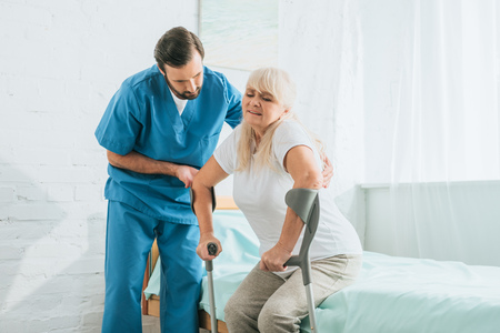 male social worker helping sick senior woman with crutches sitting on hospital bed