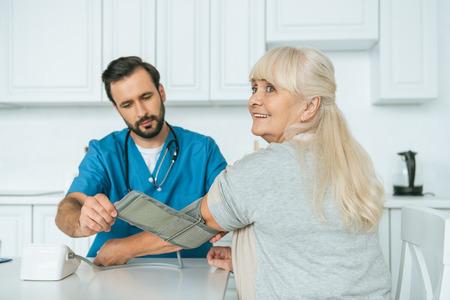 caregiver measuring blood pressure to smiling senior woman