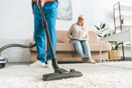 cropped shot of man using vacuum cleaner while senior woman sitting on sofa