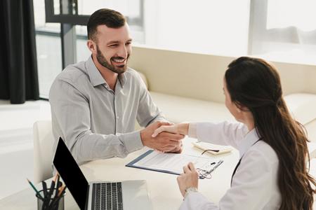 Cliente sonriente un apretón de manos con el médico en el consultorio con un portátil y un formulario de reclamación de seguros
