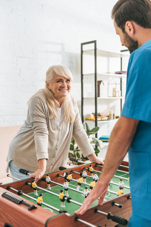 smiling senior woman playing table football with social worker