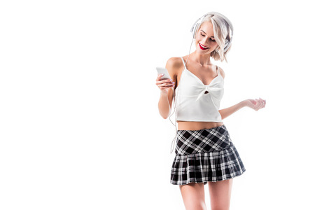 portrait of seductive schoolgirl with smartphone listening music in headphones isolated on white Banque d'images - 109569902