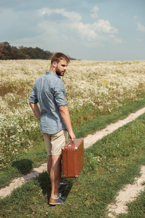 back view of man with retro suitcase standing in filed with wild flowers on summer day