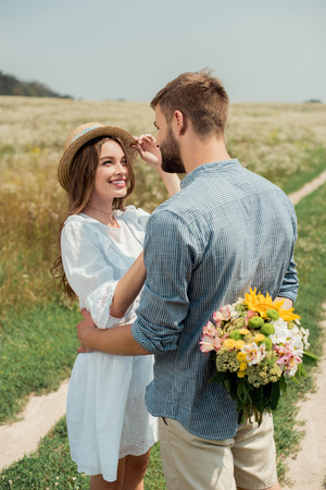 man hiding bouquet of wild flowers for smiling girlfriend behind back in summer field 스톡 콘텐츠