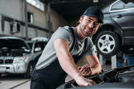 smiling auto mechanic working with car in repair shop 스톡 콘텐츠