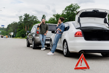 drivers talking by smartphones on road after car accident Stock Photo