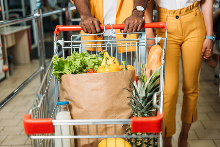 cropped image of young couple carrying shopping trolley with food in supermarket