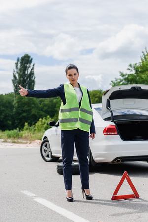 attractive businesswoman in light green vest hitchhiking on road near broken car