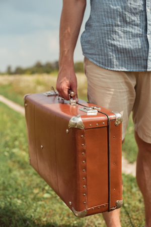 cropped shot of man holding retro suitcase in filed with wild flowers on summer day Stock fotó