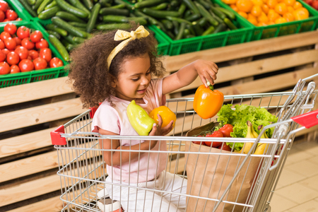 smiling african american kid putting bell peppers in paper bag while sitting in shopping trolley in supermarket Stock Photo