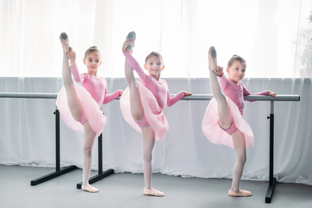 beautiful little ballet dancers exercising and looking at camera in ballet school Фото со стока - 109572122