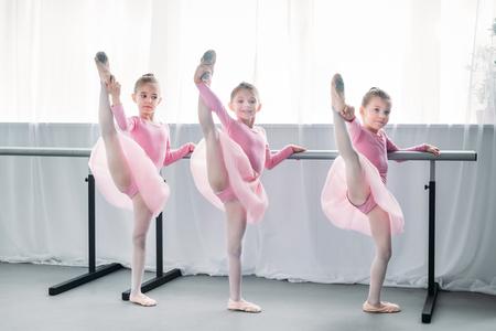 mooie kleine balletdansers oefenen en kijken naar de camera in de balletschool