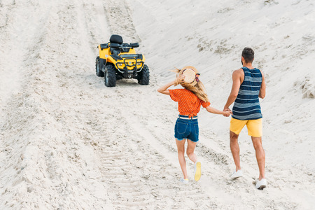 rear view of young couple going to ATV by sandy dune Stock fotó - 109572153