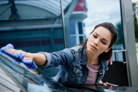 beautiful woman cleaning car at car wash with rag