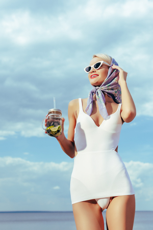 attractive girl in white vintage swimsuit holding mason jar with cocktail 스톡 콘텐츠