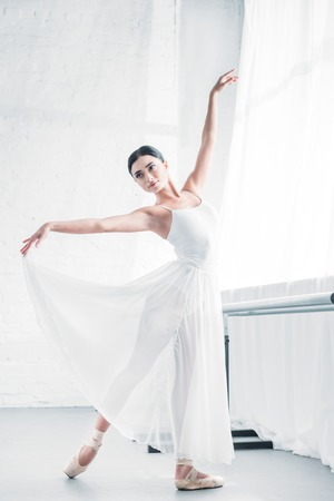 elegant young ballerina in white dress dancing in ballet studio