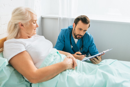 doctor writing on clipboard while sick senior woman lying in hospital bed