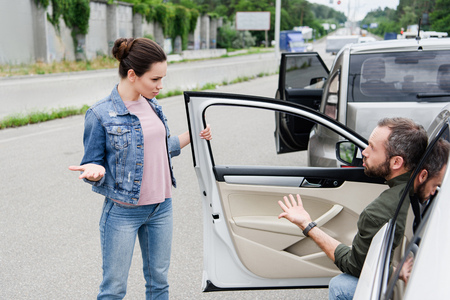 male and female drivers quarreling and gesturing on road after car accident