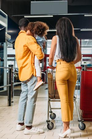 vista posteriore della famiglia afro-americana con carrello della spesa in un supermercato Archivio Fotografico