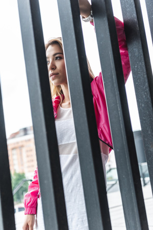 low angle view of attractive stylish asian woman standing near metal fence at urban street