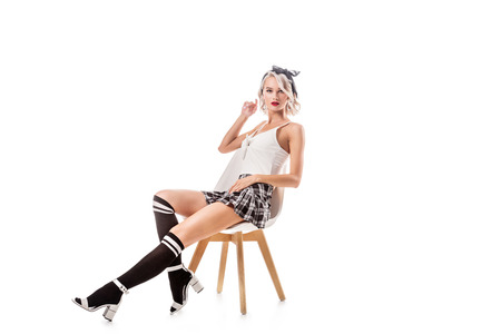 young blond woman in sexy short plaid skirt and knee socks sitting on chair isolated on white Stockfoto
