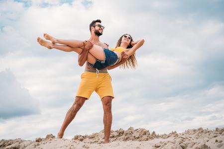 Apuesto joven llevando a su novia y caminando por una duna de arena