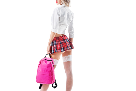 cropped shot of seductive woman in short schoolgirl skirt ad stockings with backpack isolated on white Фото со стока
