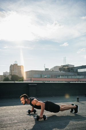 side view of handsome athletic sportsman doing plank on dumbbells on roof