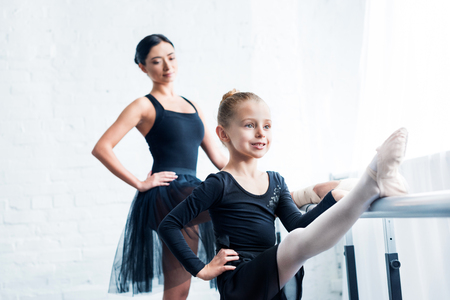 smiling little ballerina stretching while teacher standing behind in ballet school