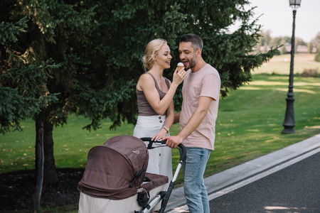 wife feeding husband with ice cream near baby carriage in park Banco de Imagens