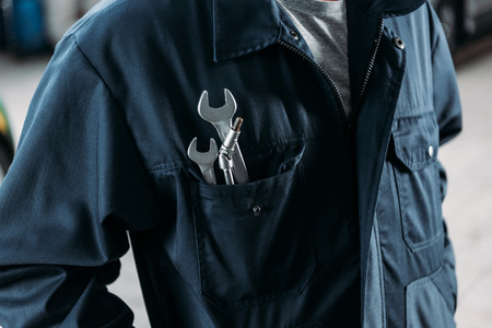 cropped view of workman in overalls with wrenches in pocket Stock Photo