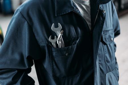 Vista recortada del trabajador en monos con llaves en el bolsillo