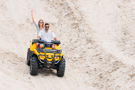 happy young couple riding ATV in desert and waving at camera Stock fotó - 109581924