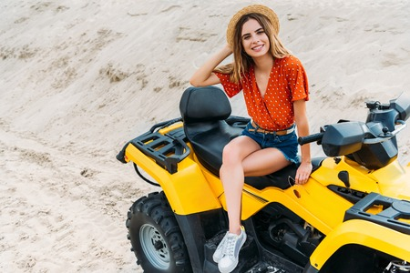 high angle view of happy young woman sitting on all-terrain vehicle on sand