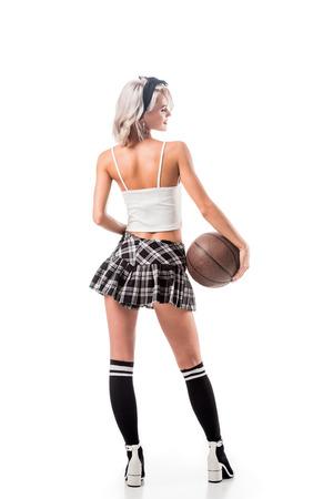 Rückansicht der verführerischen Frau im kurzen Schulmädchenrock mit Basketballball lokalisiert auf Weiß