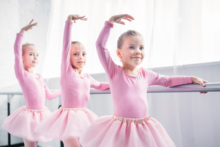 adorable smiling children in pink tutu skirts dancing in ballet studio