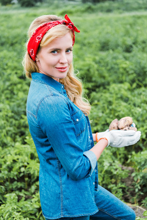 attractive farmer holding ripe potatoes in field at farm and looking at camera Фото со стока