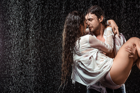 portrait of young man holding girlfriend in white shirt while standing under rain isolated on black Standard-Bild