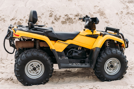 side view of modern yellow all-terrain vehicle standing in desert on cloudy day 스톡 콘텐츠