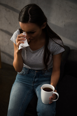 upset woman crying and holding napkin and cup of coffee Stockfoto