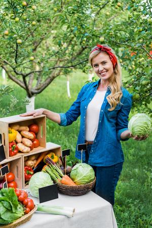 attractive farmer holding cabbage at farmer market