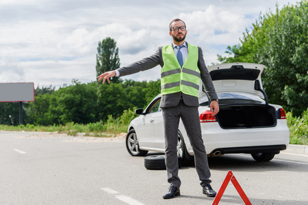 handsome businessman in light green vest stopping car on road Stock Photo