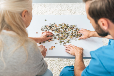cropped shot of senior woman and young caregiver playing with jigsaw puzzle pieces Reklamní fotografie