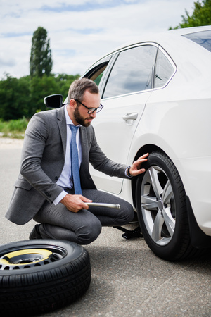 handsome businessman changing tires on car on road
