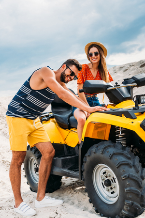 handsome young man pushing atv with his girlfriend got stuck in desert Reklamní fotografie