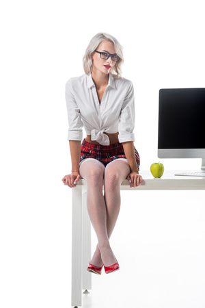 sexy schoolgirl in short plaid skirt sitting on table with fresh apple and blank computer screen isolated on white