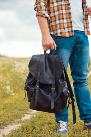partial view of man in jeans holding black leather backpack in field Stock fotó - 109613971